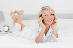 Happy woman making a phone call lying on bed Stock Photo