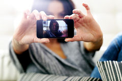 Happy woman making self photo with her smartphone. Focus on smartphone. Stock Photo