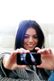 Happy woman making self photo with her smartphone Royalty Free Stock Photo