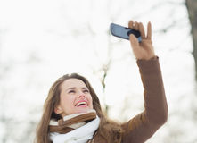 Happy woman making self photo in winter outdoors Stock Photos