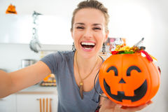 Happy woman making selfie with halloween bucket full of candy Stock Photo
