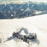 Happy woman making snow angel in the snow mountain. Ski. Stock Photography