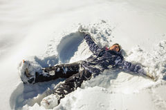 Happy woman making snow angel in the snow. Ski. Funny female skier on the background of high snow-capped Alps in Swiss Stock Photography