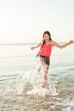 Happy woman making splashes on the beach Royalty Free Stock Images