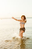 Happy woman making splashes on the beach Stock Photos