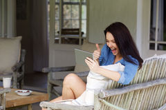 Happy woman making video call using touchscreen tablet Royalty Free Stock Images