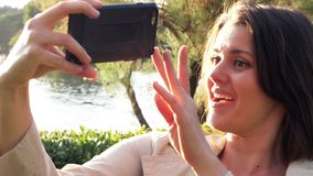 Happy woman making video phone call from lake in park in vacation in European country closeup stock video