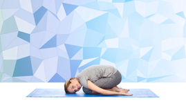 Happy woman making yoga in child pose on mat Royalty Free Stock Images