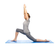 Happy woman making yoga in low lunge on mat Stock Photo