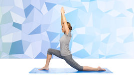 Happy woman making yoga in low lunge on mat Royalty Free Stock Photos