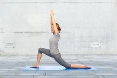 Happy woman making yoga in low lunge on mat Royalty Free Stock Photo