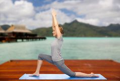 Happy woman making yoga in low lunge outdoors. Fitness, sport, people and healthy lifestyle concept - happy woman making yoga in low lunge pose on wooden pier stock images