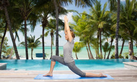 Happy woman making yoga in low lunge over beach. Fitness, sport, people and healthy lifestyle concept - happy woman making yoga in low lunge pose on mat over stock photos