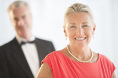 Happy Woman With Man In Background At Home Stock Photography