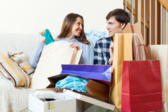 Happy woman and man with clothes and shopping bags. Happy women and men with clothes and shopping bags in home interior Stock Photos