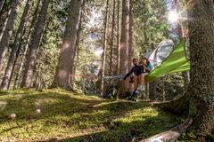 Happy woman man couple relaxing in hanging tent camping in forest woods during sunny day.Group of friends people summer. Happy women men couple relaxing in stock photos