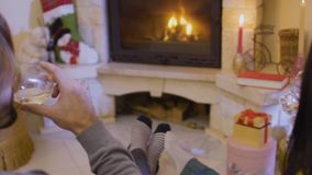 Happy woman with man drinks wine enjoying relax near fireplace. Happy married couple sits on the floor near the fireplace and drinks wine. Husband and wife have stock footage