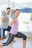Happy woman and man exercising with barbells Stock Photos