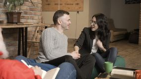 Happy woman and man makes peace at psychologist`s reception. Married couple sits on the sofa in bean bags at a psychologist`s reception. People tells about their stock footage