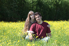 Happy woman and man sit among yellow flowers at meadow Royalty Free Stock Photos