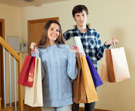 Happy woman and man together with shopping bags. Happy women and men together with shopping bags in home interior Royalty Free Stock Images
