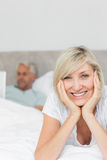 Happy woman with man using laptop in bed Stock Images