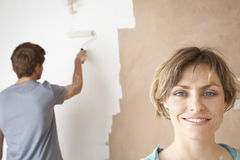 Happy Woman With Man Using Paint Roller On Wall Royalty Free Stock Image