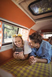 Happy woman with man using phone in van Royalty Free Stock Image