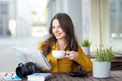 Happy woman with map drinking cocoa at city cafe Royalty Free Stock Photos