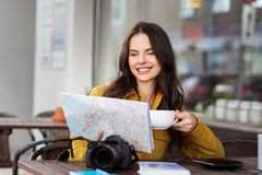 Happy woman with map drinking cocoa at city cafe stock photo
