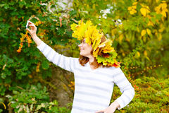 Happy woman with maple leaves garland making selfie Royalty Free Stock Photos