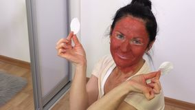 Happy Woman with a mask from clay on her face stock video footage