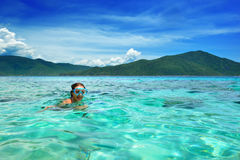 Happy woman with a mask floating in the azure tropical sea Stock Photos