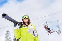 Happy woman in mask with ski lift behind her Stock Photography