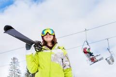Happy woman in mask with ski lift behind her. Happy woman in mask standing and holding ski with ski lift behind at Krasnaya polyana ski resort and Caucasus Stock Photography