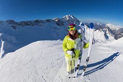 Happy woman in mask standing and holding ski. And ski poles during sunny winter day on Krasnaya polyana ski resort and Caucasus mountains in Sochi, Russia Royalty Free Stock Photos