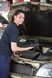 Happy Woman Mechanic with Diagnostic Tool. A happy female mechanic looking at the camera using a diagnostic scan tool stock image