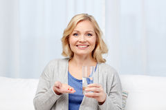 Happy woman with medicine and water glass at home Stock Images