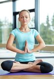 Happy woman meditating in lotus pose on mat Stock Photos