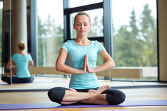 Happy woman meditating in lotus pose on mat Stock Photo