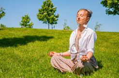 Happy woman is meditating sitting in Lotus pose on grass lawn. Beautiful boho style woman with accessories enjoy summer sunny day stock image