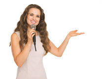 Happy woman with microphone pointing on copy space Stock Photos