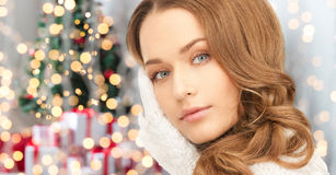 Happy woman in mittens over christmas lights Stock Image