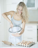 Happy woman mixing cookie batter in kitchen at counter Stock Images