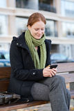 Happy Woman with a Mobile Phone in a City Stock Images