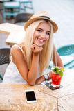 Happy woman with mobile phone drinking cocktail in outdoor cafe Royalty Free Stock Images