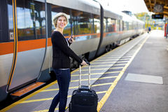 Happy Woman With Mobile Phone And Luggage At Train Station Royalty Free Stock Images