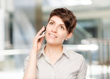 Happy woman with mobile phone and space left. In the office Royalty Free Stock Images