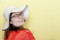 Happy Woman Model on Bright Yellow Background with Copy Space. Colorful Yellow wall and bright coral shirt, smiling and wearing a sun hat. Has space for copy Stock Photography