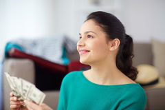 Happy woman with money planning her travel at home Royalty Free Stock Photography